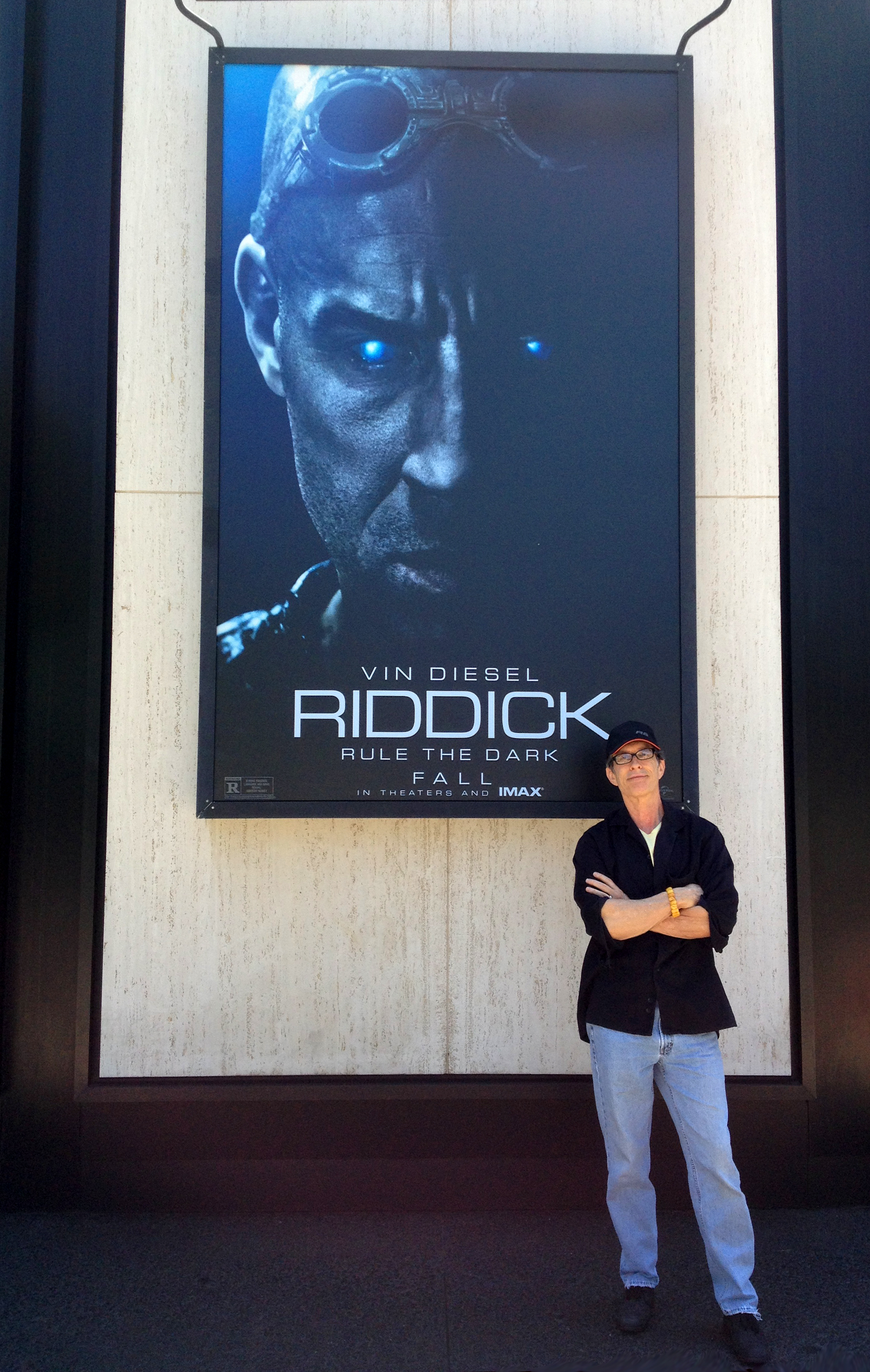 David Twohy on Universal Lot with giant poster of his movie, August 2013